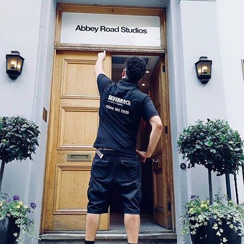 Silverback crew member pointing at Abbey Road Studios door